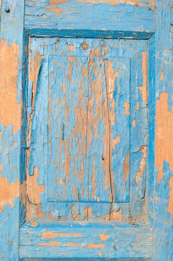 Fragmentet av den gamla trädörren med spruckna blått målar royaltyfria bilder