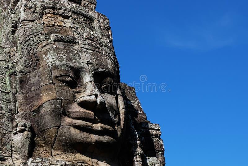 Fragmentet av det forntida stenar templet Bayon i Cambodja v?nd stenen mot Framsidan av en man, vikt med stenkvarter arkivfoto