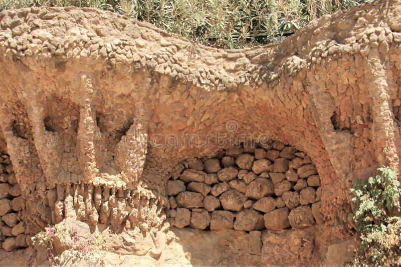 Fragmentet av en stenvägg med en original- design parkerar in Guell, Barcelona, Spanien royaltyfri foto