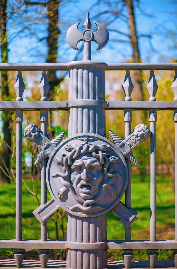 Fragmentet av ett metallstaket av sommarträdgården i St Petersburg dekorerade med bilden av framsidan av Gorgon Medusa på fotografering för bildbyråer