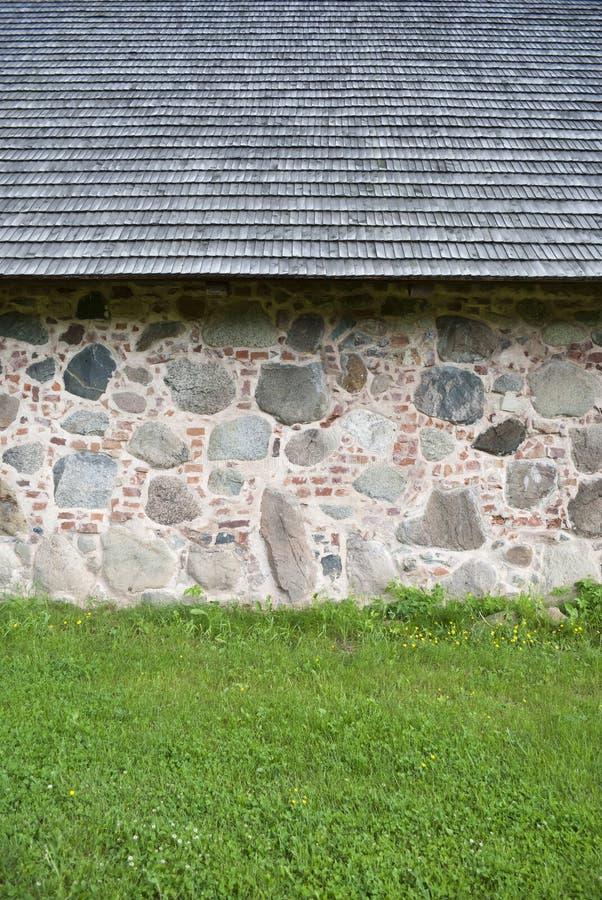 Fragmentet av väggen av huset satte från stora granitstenar royaltyfria foton