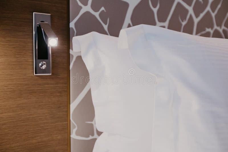 Fragmento ascendente cercano del dormitorio con la lámpara de lectura en hogar u hotel moderno fotos de archivo