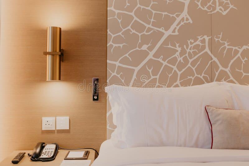 Fragmento ascendente cercano del dormitorio con la lámpara de lectura en hogar u hotel moderno imagen de archivo