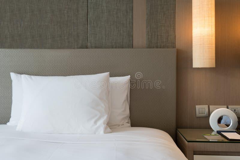 Fragmento ascendente cercano del dormitorio con la lámpara de lectura y el despertador digital en hogar u hotel moderno fotografía de archivo