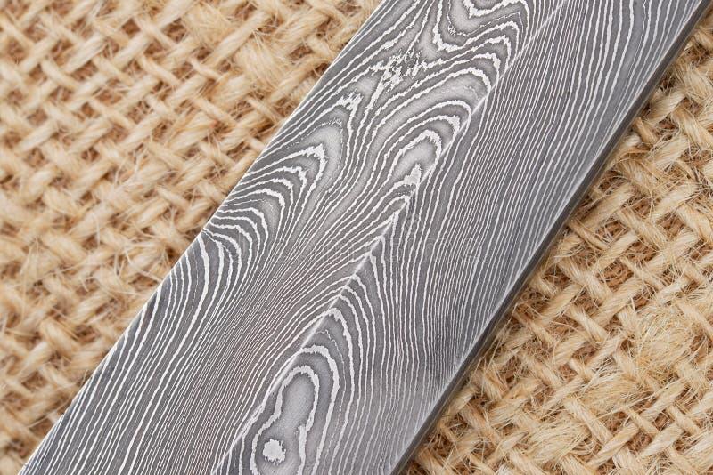 Fragmento da lâmina de faca finlandesa feito a mão tradicional com o teste padrão de onda abstrato do aço de Damasco sobre um bac fotografia de stock