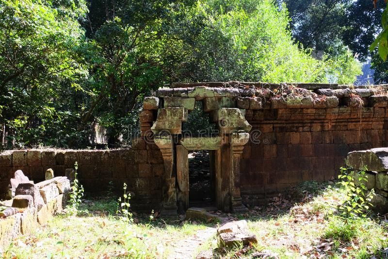 Fragmento da parede dilapidada velha com uma entrada pequena Dia morno ensolarado na floresta fotos de stock royalty free