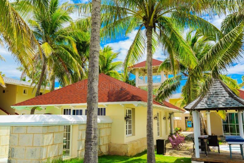 Fragmento de invitación hermoso de la vista del chalet del jardín, área de servicio real en jardín tropical cerca de la playa imágenes de archivo libres de regalías