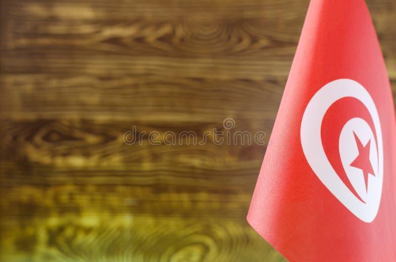 Fragmento de la bandera tunecina en el primer plano para el fondo borroso del texto imágenes de archivo libres de regalías