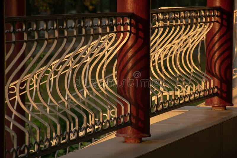 Fragmento de la cerca con las columnas del metal Dibujo de la luz y de la sombra fotografía de archivo