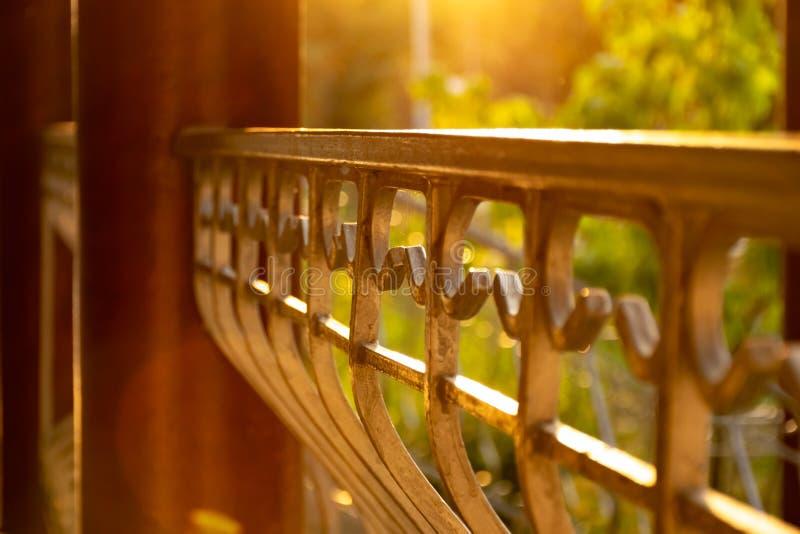 Fragmento de la cerca en los rayos de la puesta del sol imagenes de archivo