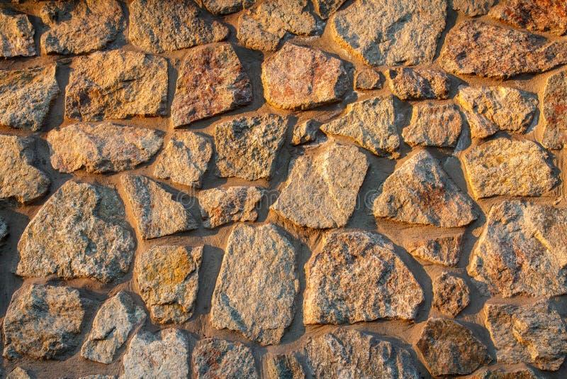 Fragmento de la pared de piedra iluminada por el sol fotografía de archivo libre de regalías
