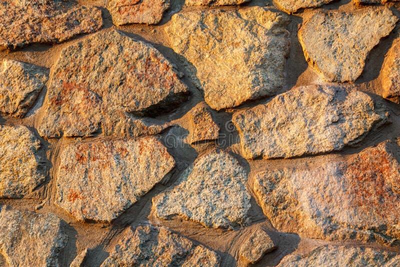 Fragmento de la pared de piedra iluminada por el sol foto de archivo libre de regalías
