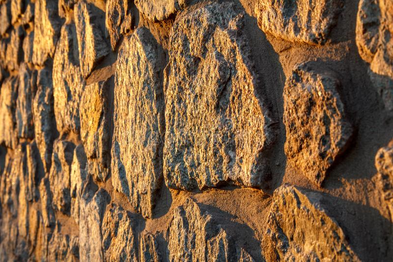 Fragmento de la pared de piedra iluminada por el sol Vista lateral imagen de archivo