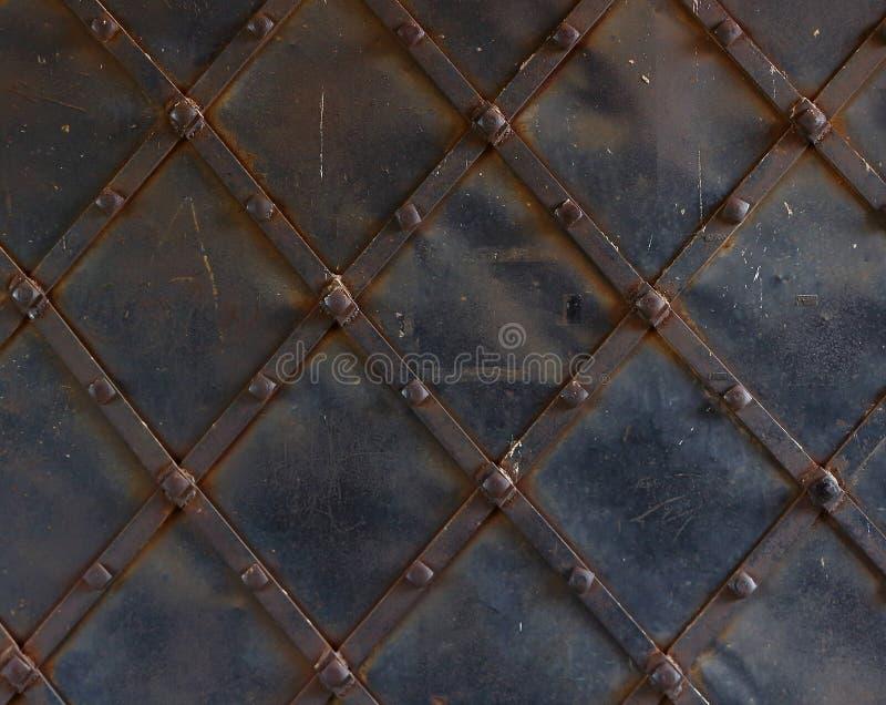 Fragmento de las puertas del metal con los remaches fotografía de archivo