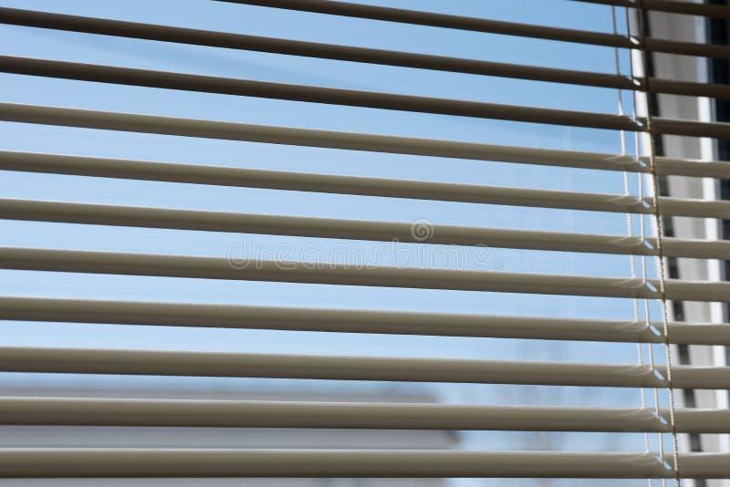 Fragmento de persianas en la ventana Usted puede ver el cielo a través de las persianas imagenes de archivo