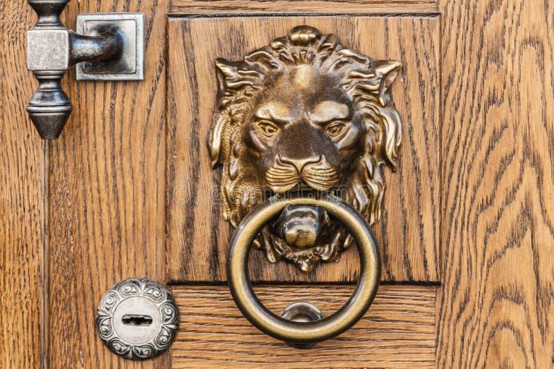 Fragmento de um amarelo e de uma porta de madeira marrom com uma aldrava de porta manual leão-dada forma do metal imagem de stock