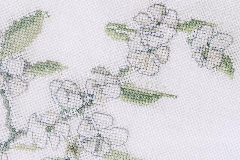 Fragmento de um bordado colorido do ponto de cruz, ornamento do verão da flor fotografia de stock royalty free