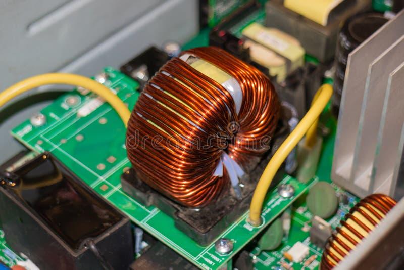 Fragmento de um circuito poderoso da fonte de alimentação, close-up da bobina da indutância fotos de stock
