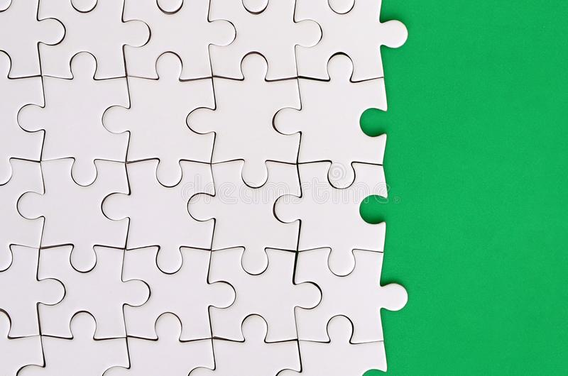 Fragmento de um enigma de serra de vaivém branco dobrado no fundo de uma superfície verde do plástico Foto da textura com espaço  foto de stock