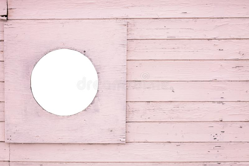Fragmento de um de madeira pintado na superfície cor-de-rosa do ciolor com um furo vazio redondo para a imagem fotos de stock royalty free