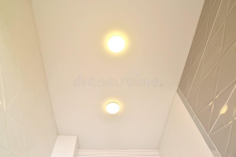 Fragmento de um teto opaco do estiramento com lâmpadas em um corredor do apartamento fotografia de stock royalty free