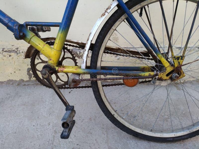 Fragmento de uma bicicleta velha pintada no amarelo, azul imagem de stock