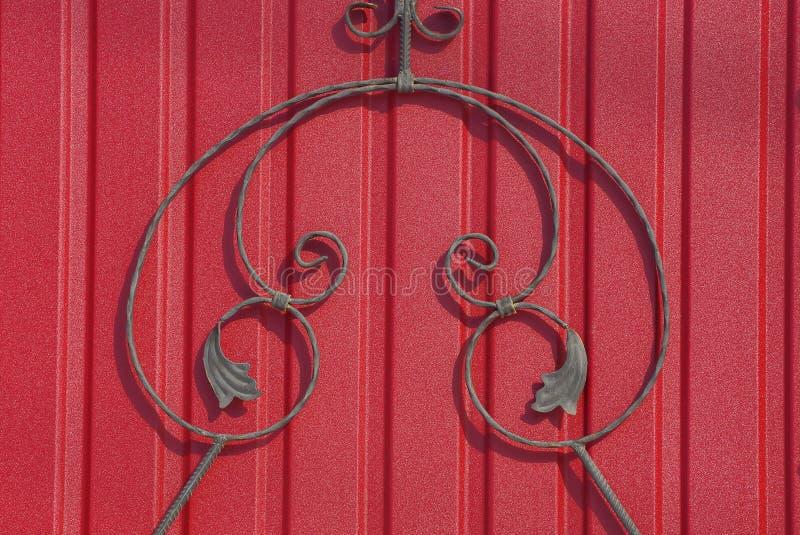 Fragmento de uma cerca com hastes forjadas em uma parede vermelha imagens de stock