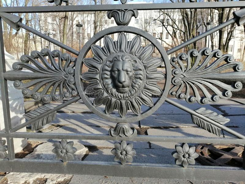 Fragmento de uma cerca do metal sob a forma de um leão foto de stock