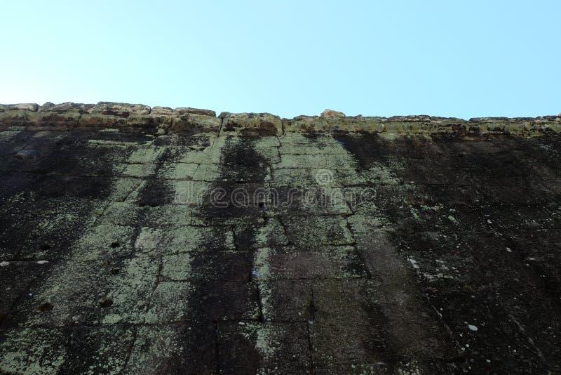 Fragmento de uma parede antiga da fortificação construída da pedra desbastada masonry Fundo fotografia de stock