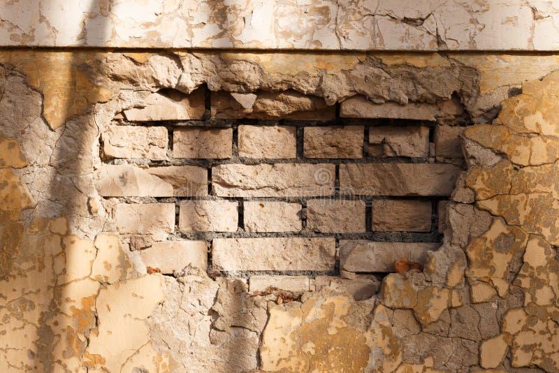Fragmento de uma parede de tijolo com emplastro desmoronado fotos de stock
