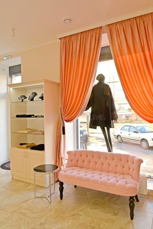 Fragmento de un interior de la tienda de la ropa del ` s de las mujeres con un maniquí en una abertura de la ventana imágenes de archivo libres de regalías