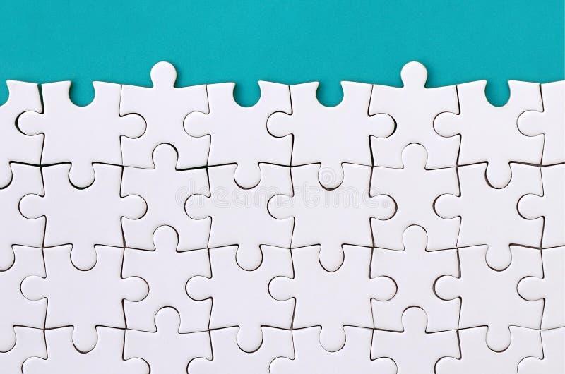 Fragmento de un rompecabezas blanco doblado en el fondo de una superficie plástica azul Foto de la textura con el espacio de la c fotografía de archivo libre de regalías