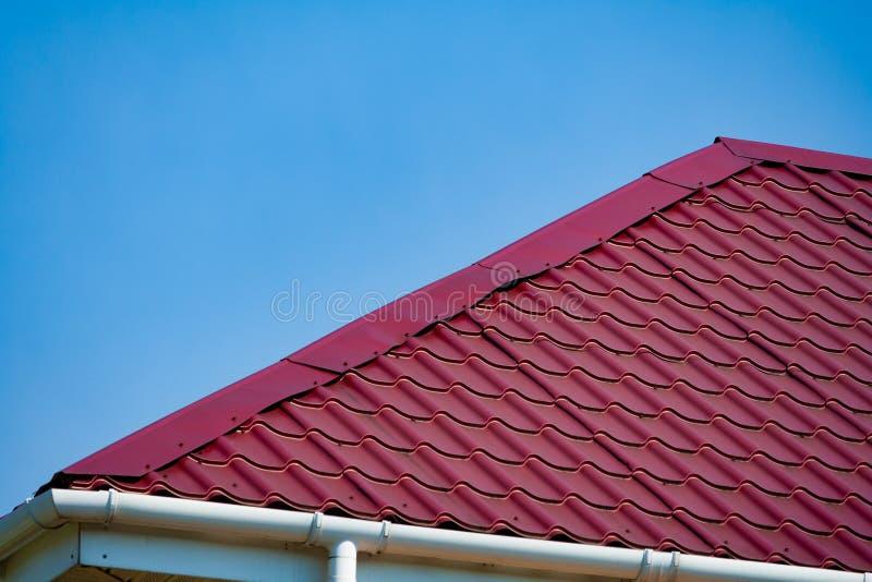 Fragmento de un tejado de teja púrpura del metal un fondo del cielo azul imagenes de archivo