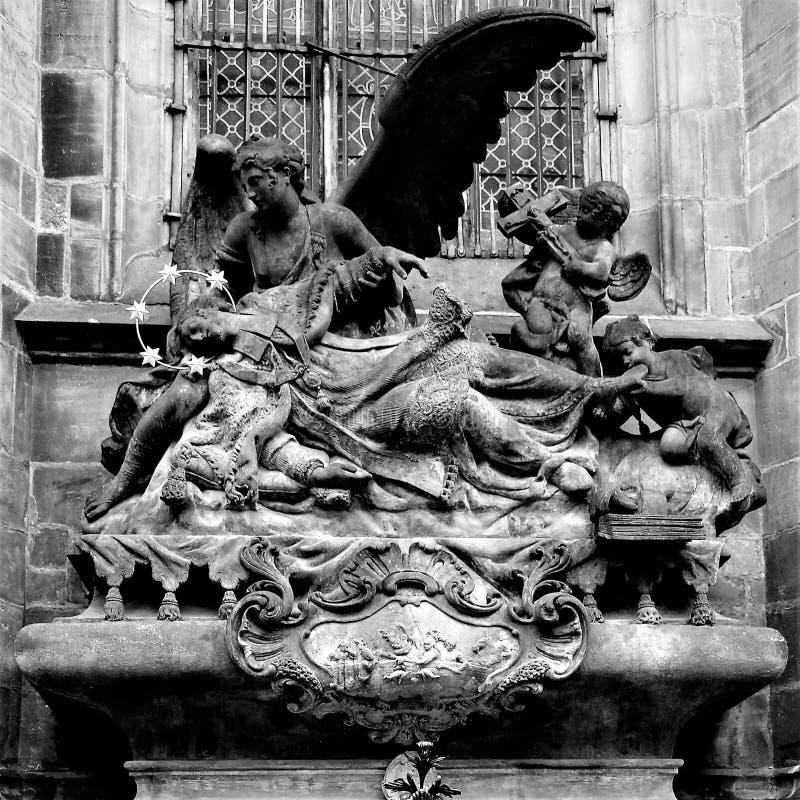 Fragmento de una composición de mármol medieval sobre el sepulcro del santo cerca de la pared de la catedral de St Vitus en Praga foto de archivo