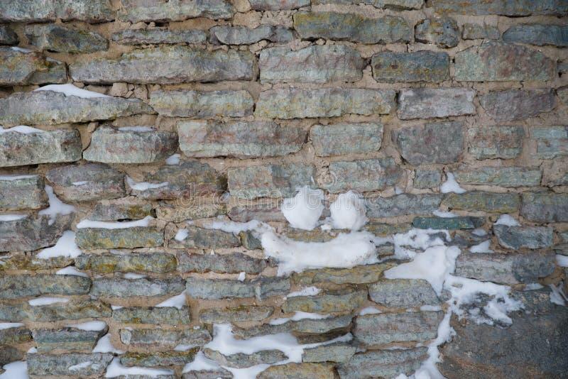 Fragmento de una pared vieja de la fortaleza con los rastros de nieve como la base del fondo fotos de archivo