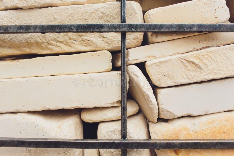 Fragmento del fondo de una pared decorativa de una piedra del granito y de un enrejado del metal foto de archivo libre de regalías