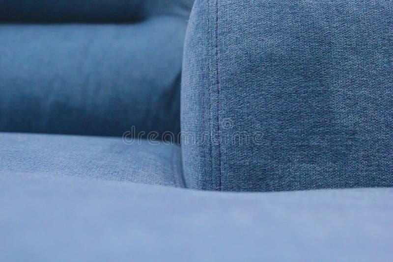 Fragmento do assento, da parte traseira e do braço do sofá azul imagens de stock