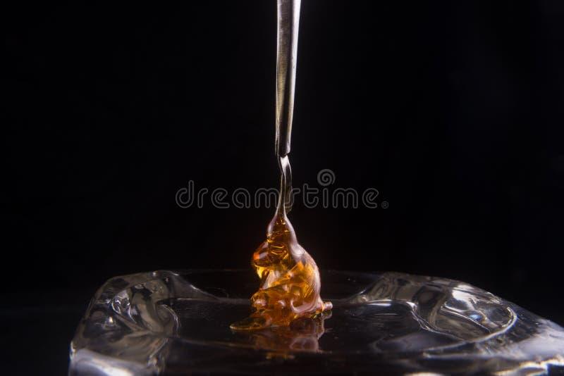 Fragmento do concentrado do óleo do cannabis aka em uma ferramenta de toque ligeiro sobre o blac imagens de stock royalty free