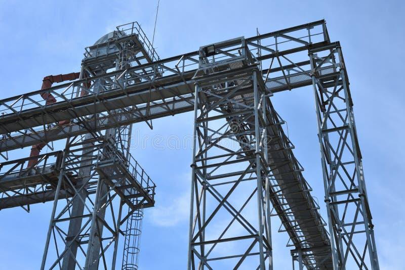 Fragmento do elevador de grão do metal na facilidade com silos imagem de stock