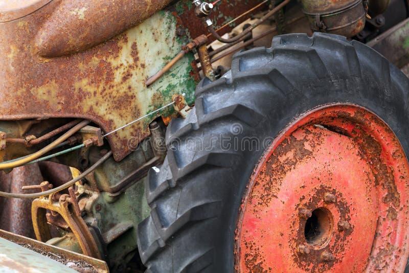 Fragmento do trator oxidado com roda vermelha imagens de stock