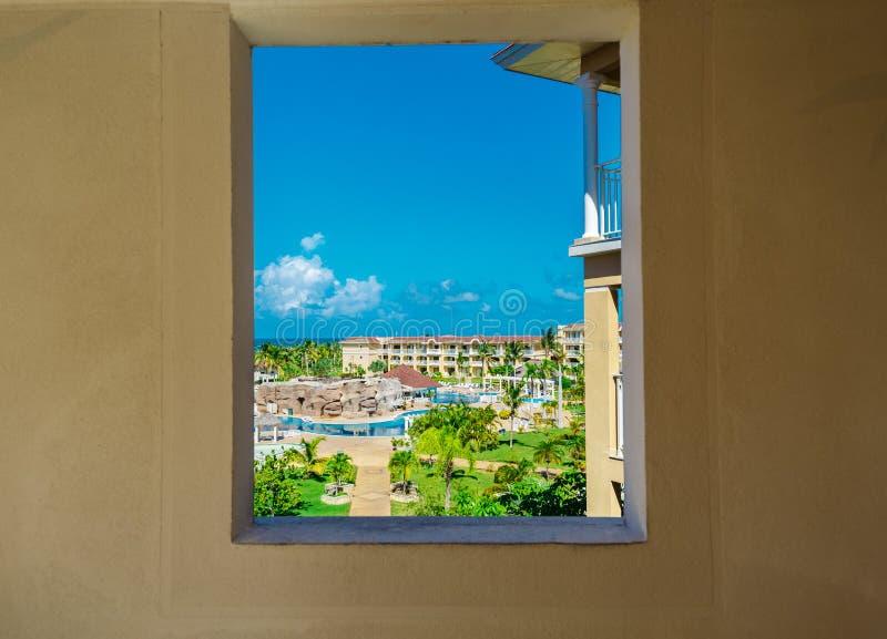 Fragmento hermoso de la vista de los argumentos tropicales del centro turístico a través de la ventana de la pared del hotel en d imagen de archivo libre de regalías