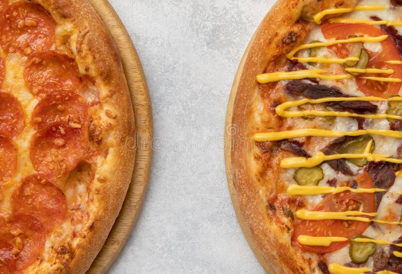 Fragmentos de dos pizzas en la tabla foto de archivo libre de regalías