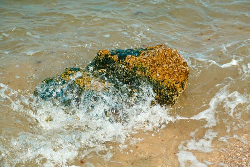 Fragmentos de piedras cerca de la orilla de mar en el lavado con agua por las ondas imagen de archivo