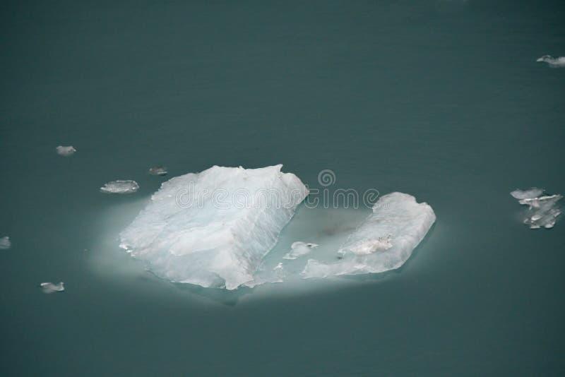 Fragmentos glaciales del iceberg de los azules turquesa en un mar del verde imagen de archivo libre de regalías