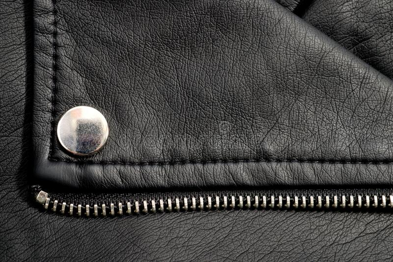 Fragments of a black artificial leather jacket with rivets and zippers. Background for clothes and metal accessories.  royalty free stock images