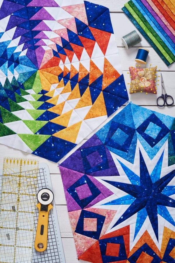 Fragments d'édredon, accessoires pour le patchwork, vue supérieure sur une surface en bois blanche images libres de droits