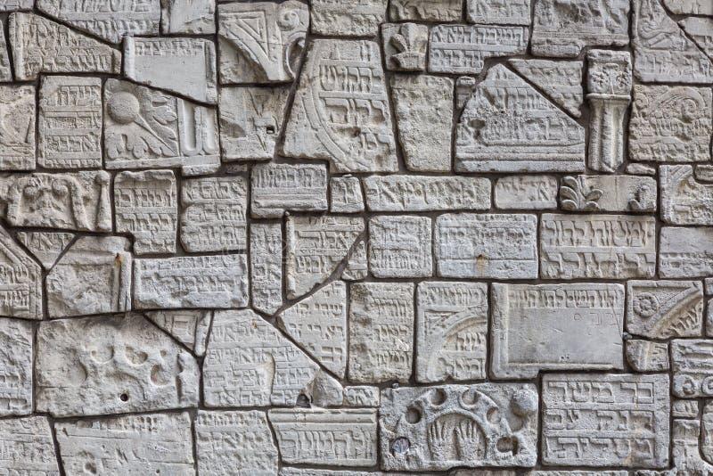 Fragments des pierres tombales juives sur un mur dans le cimetière juif photographie stock libre de droits
