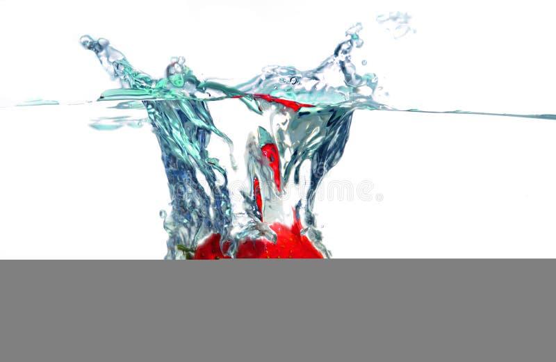 Fragola che cade in acqua immagini stock libere da diritti