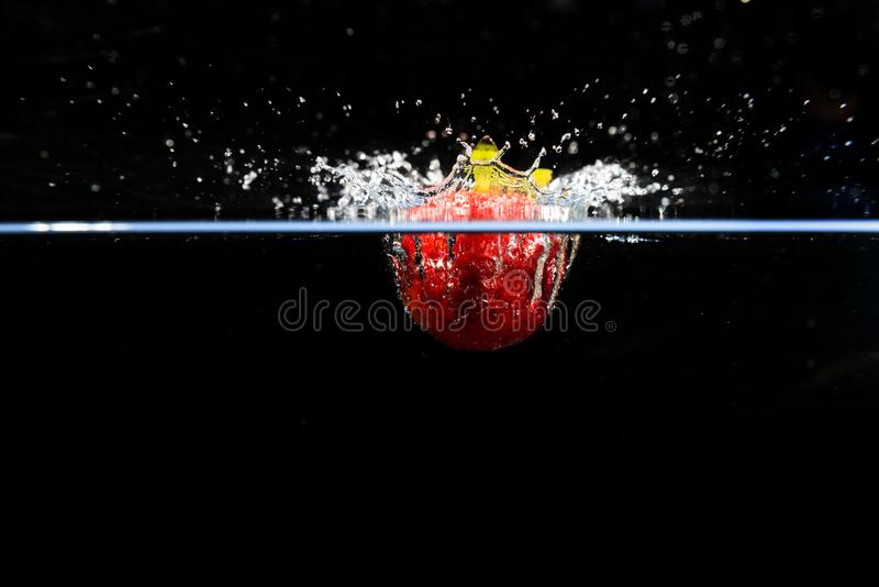 Fragola che cade nell'acqua e che spruzza le gocce sulla b nera fotografie stock