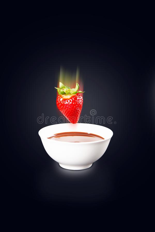 Fragola che cade nella salsa di cioccolato immagine stock